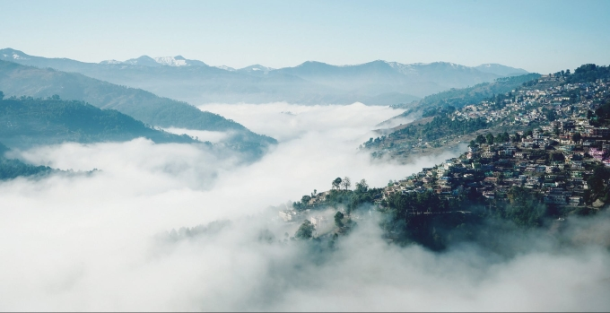 misty valley with town on slope
